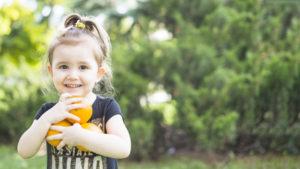 weerstand boost, sinaasappels, glimlachend-meisje-die-verse-sinaasappelen-in-het-park-houden_23-2147893029