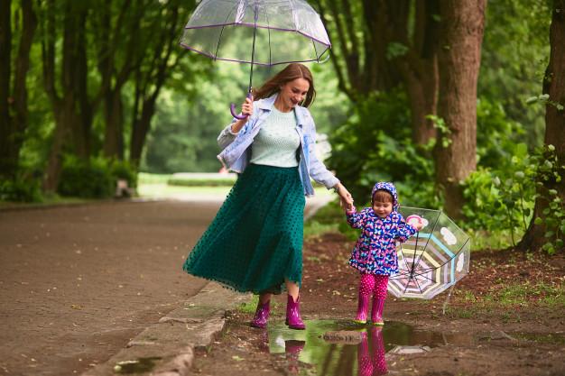 goede voornemens, meisje paraplu, meisje regenlaarzen, jonge-moeder-en-dochtertje-wandelen-na-de-regen-met-parasols-op-de-zwembaden_8353-7564