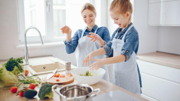 goede voornemens, koken meisje, samen koken, mooie-moeder-in-een-blauw-shirt-en-schort-bereidt-thuis-een-verse-groente-salade_1157-13945